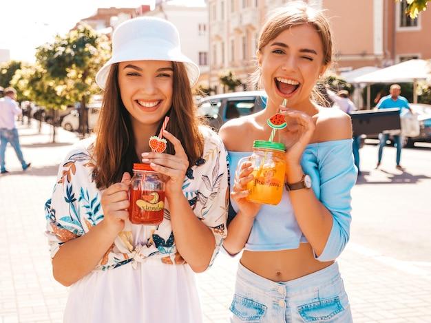 Duas jovens bonitas hipster garotas sorridentes em roupas da moda verão e chapéu panamá.