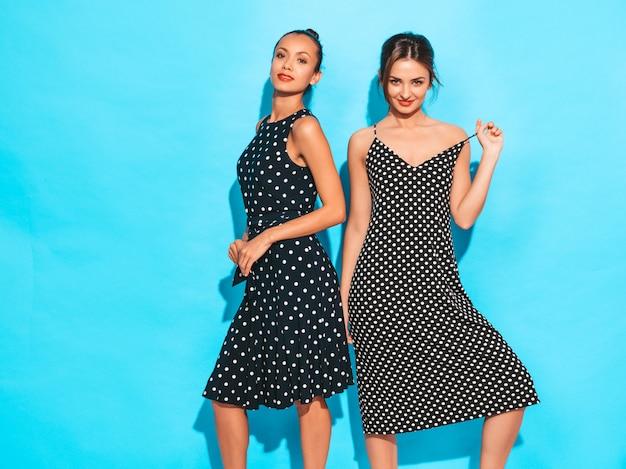 Duas jovens bonitas hipster garotas sorridentes em vestidos de bolinhas na moda verão. mulheres despreocupadas sexy posando perto da parede azul. divertindo-se e abraçando. modelos mostra bom relacionamento. fêmea com lábios vermelhos
