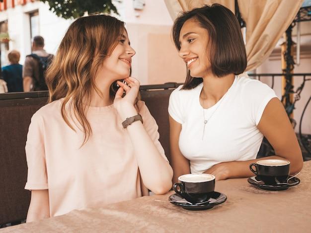 Duas jovens bonitas hipster garotas sorridentes no vestido de verão na moda. mulheres despreocupadas conversando no café da varanda e tomando café. modelos positivos se divertindo e se comunicando