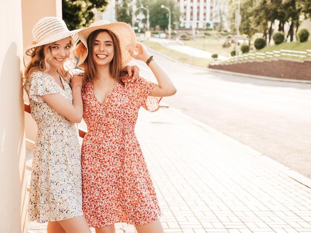 Duas jovens bonitas hipster garotas sorridentes no vestido de verão na moda. mulheres despreocupadas sexy posando no fundo da rua em chapéus. modelos positivos se divertindo e abraçando