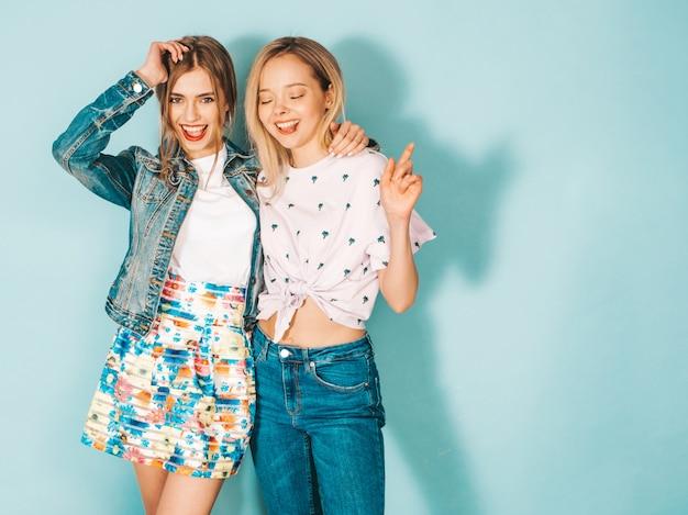 Duas jovens bonitas loiras garotas hipster sorridente em roupas coloridas na moda verão.
