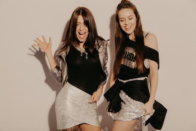 Duas jovens bonitas loiras garotas hipster sorridente em roupas da moda no verão. mulheres despreocupadas sexy posando perto da parede no estúdio. modelos positivos se divertindo