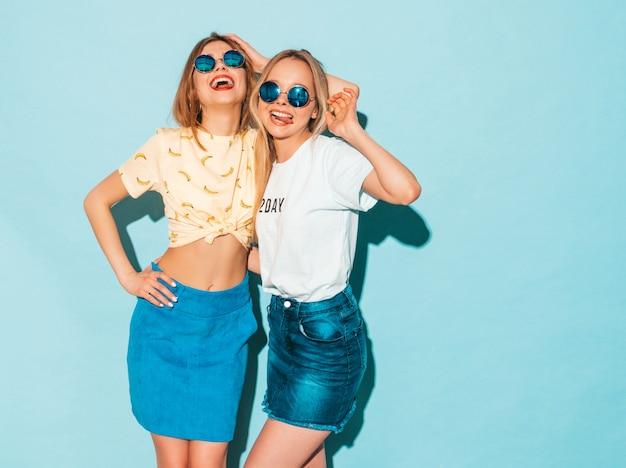 Duas jovens bonitas loiras hipster loiras em jeans na moda verão saias roupas.
