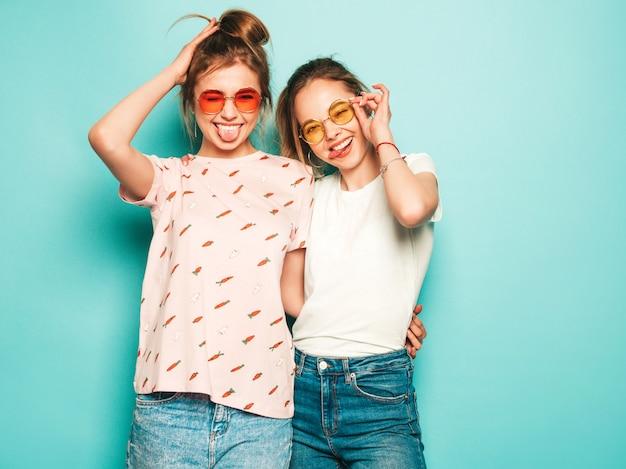 Duas jovens bonitas loiras sorridentes garotas hipster em roupas da moda verão hipster jeans. mulheres despreocupadas