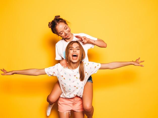 Duas jovens bonitas sorridentes garotas hipster em roupas da moda no verão. mulheres despreocupadas sexy posando perto da parede amarela. modelo sentado nas costas da amiga e levantando as mãos