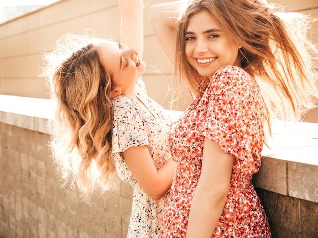 Duas jovens bonitas sorrindo garotas hipster em vestido de verão na moda. mulheres despreocupadas sexy posando no fundo da rua. modelos positivos se divertindo e enlouquecendo
