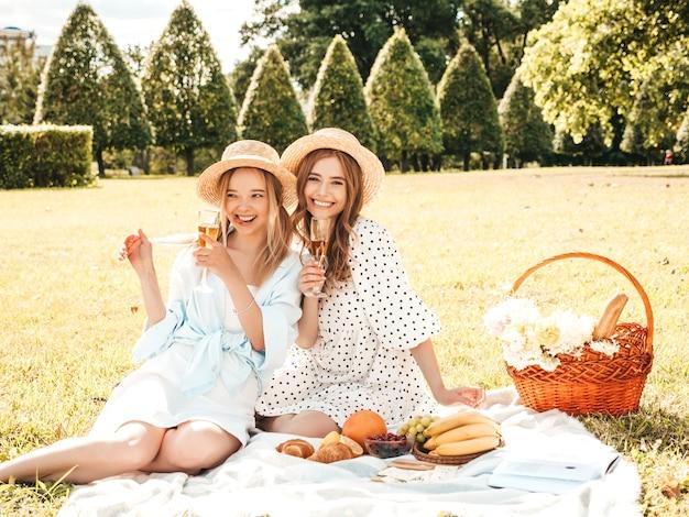 Duas jovens bonitas sorrindo hipster fêmea com vestido de verão e chapéus. mulheres despreocupadas fazendo piquenique do lado de fora.