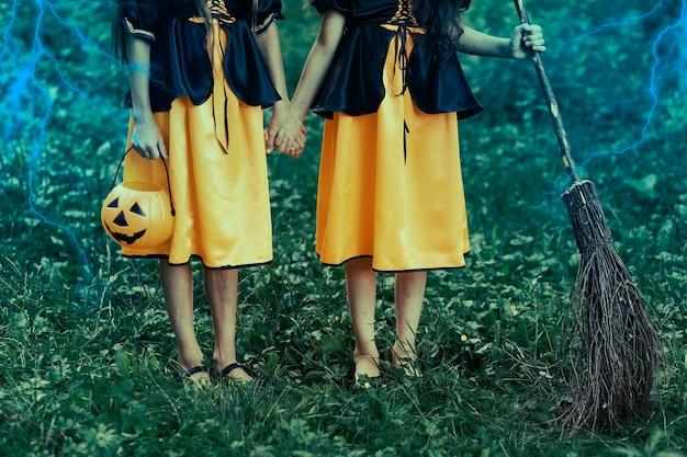 Duas jovens bruxas na floresta no dia das bruxas