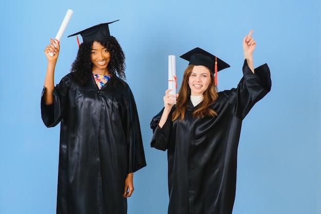 Duas jovens celebrando a formatura com diplomas