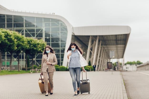 Duas jovens com malas voltam de uma viagem de negócios durante a quarentena