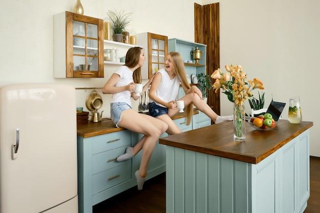 Duas jovens contando histórias e rindo na cozinha