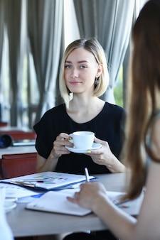 Duas jovens conversando, sentadas à mesa no café