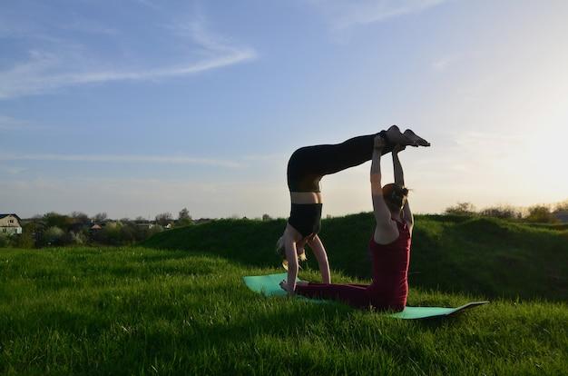 Duas jovens de cabelos louro em ternos de desporto praticam ioga
