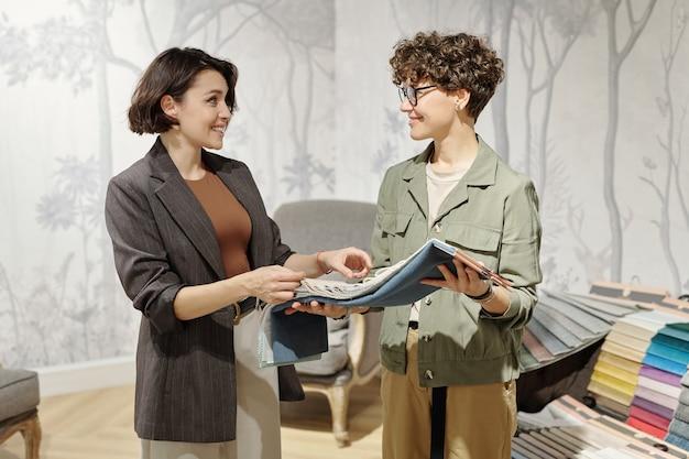 Duas jovens designers de interiores felizes em um estúdio, dando consultoria enquanto escolhem amostras de têxteis para móveis novos