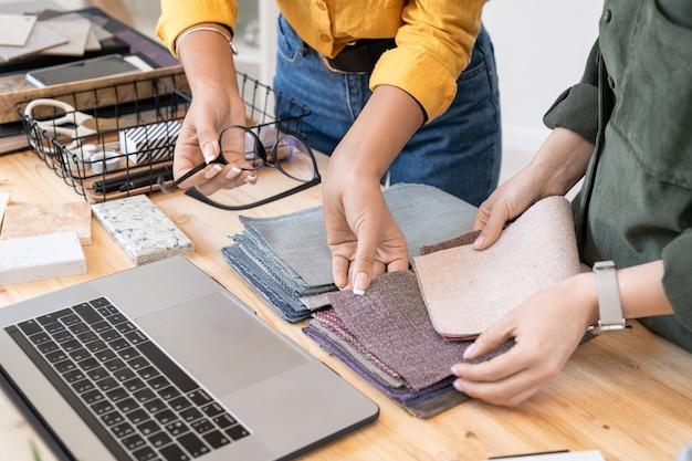 Duas jovens designers de roupas casuais escolhendo amostras de têxteis para móveis enquanto trabalham em um novo pedido à mesa no estúdio