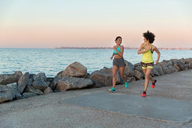 Duas jovens desportistas correndo juntos e conversando