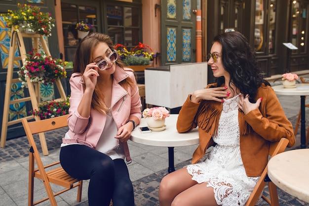 Duas jovens elegantes sentadas em um café