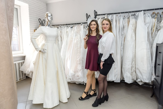 Duas jovens em pé perto de um manequim em um salão de casamento
