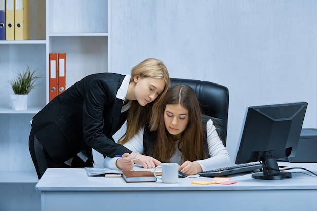 Duas jovens empresárias buscam em conjunto uma solução para o problema, trabalhando juntas no escritório