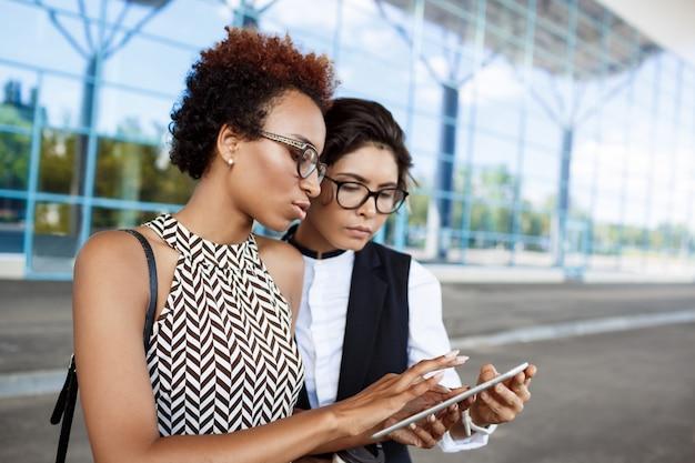 Duas jovens empresárias de sucesso olhando tablet sobre o centro de negócios.