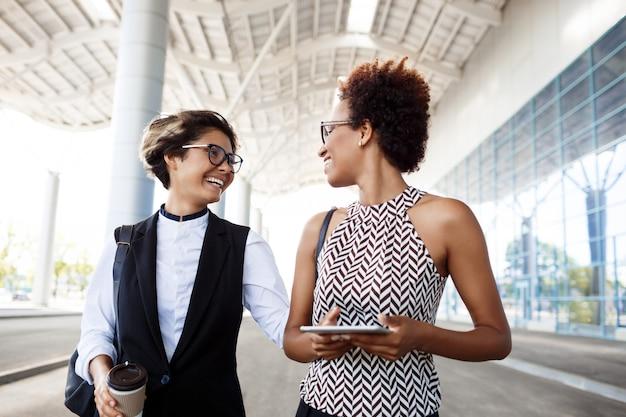 Duas jovens empresárias de sucesso rindo, sorrindo sobre o centro de negócios.