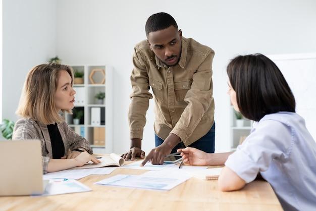 Duas jovens empresárias ouvindo a explicação de sua colega africana durante a discussão de documentos e dados financeiros na reunião