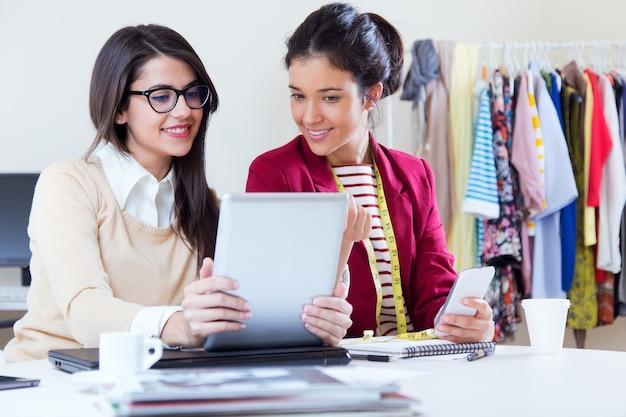 Duas jovens empresárias que trabalham com tablet digital em seu escritório.