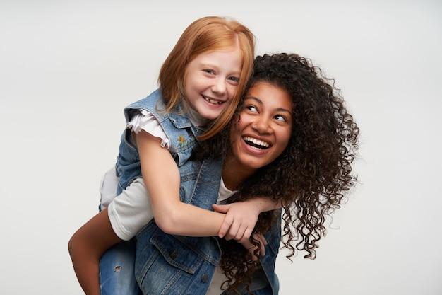 Duas jovens encantadoras senhoras alegres em coletes jeans e camisas brancas, regozijando-se e rindo alegremente em pé sobre o branco, mostrando seus dentes brancos enquanto sorriem amplamente