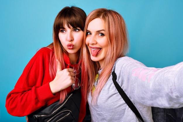 Duas jovens engraçadas e bonitas mulheres hipster vestindo roupas casuais brilhantes e esportivas, sorrindo, gritando e dizendo oi para você, parede azul