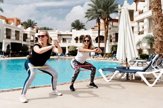 Duas jovens esportistas fazendo exercícios com elástico