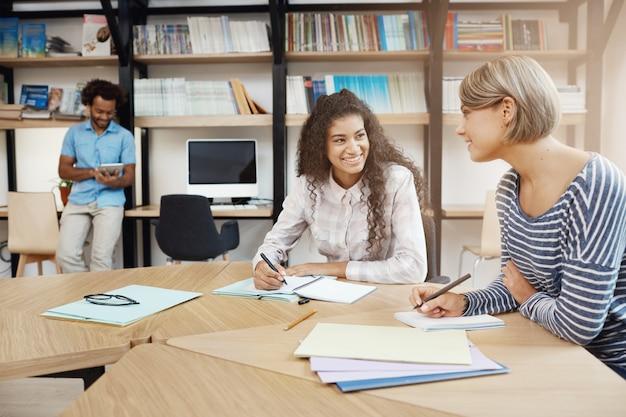 Duas jovens estudantes multiétnicas bonitas falando sobre projeto de graduação, fazendo anotações em cadernos, procurando informações em livros.