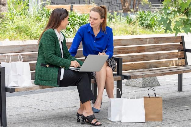Duas jovens executivas verificando seus laptops enquanto conversam depois de fazer compras com sacolas de compras