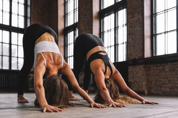 Duas jovens fazem complexo de alongamento asanas de ioga na aula de estilo loft