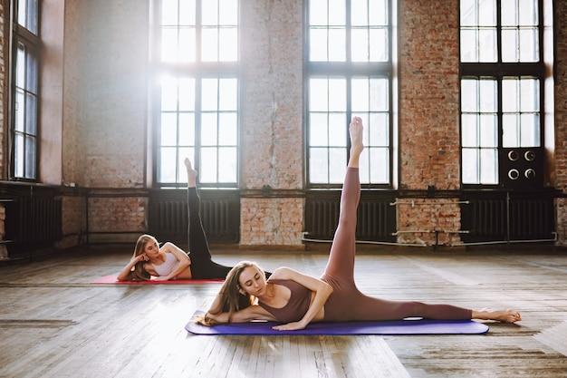 Duas jovens fazem complexo de alongamento asanas de ioga na aula de estilo loft.