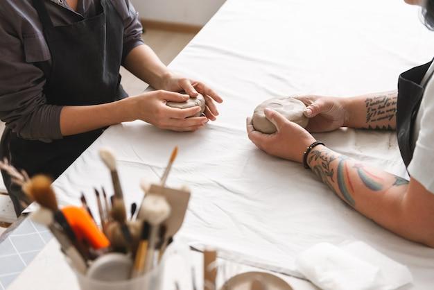 Duas jovens fazendo panela de barro na oficina de cerâmica