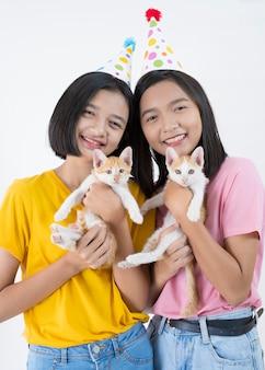 Duas jovens felizes usam camisa rosa e amarela e chapéu de festa com dois gatos