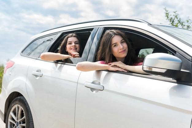 Duas jovens felizes viajando de carro