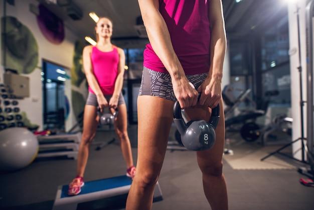 Duas jovens forma atlética atraente slim aptidão ativo meninas fazendo exercícios com kettlebells