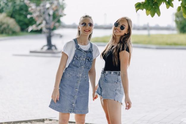 Duas jovens garotas bonitas em uma caminhada no parque. um dia ensolarado de verão, alegria e amizades.