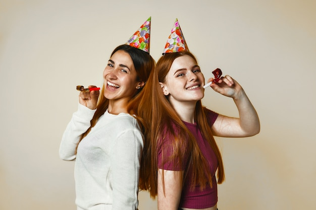 Duas jovens garotas caucasianas em chapéus de aniversário estão sinceramente sorrindo