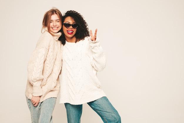 Duas jovens garotas hippie sorridentes bonitas em suéteres de inverno da moda. modelos positivos se divertindo e se abraçando