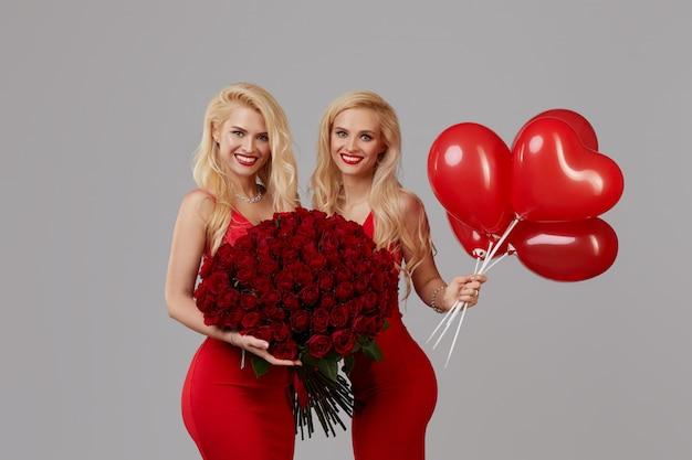 Duas jovens gêmeas felizes com um grande buquê de rosas vermelhas e um coração vermelho em forma de balões.