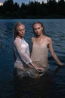 Duas jovens irmãs gêmeas com longos cabelos loiros posando em vestidos leves na água do lago à noite de verão