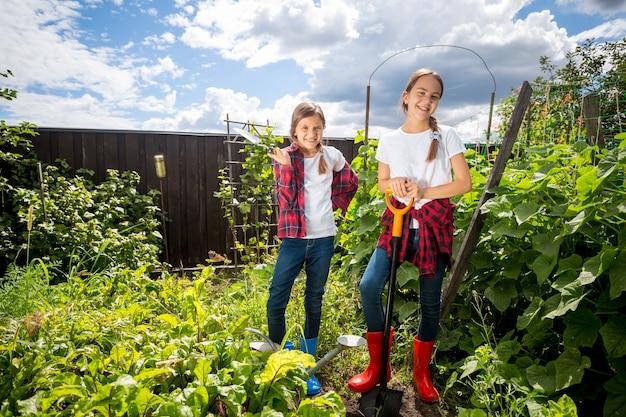 Duas jovens irmãs trabalhando no jardim de um quintal em um dia de sol