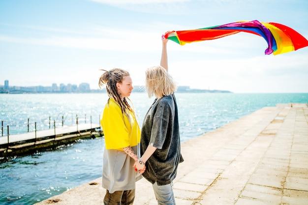 Duas jovens lésbicas de mãos dadas na praia segurando uma bandeira de arco-íris.