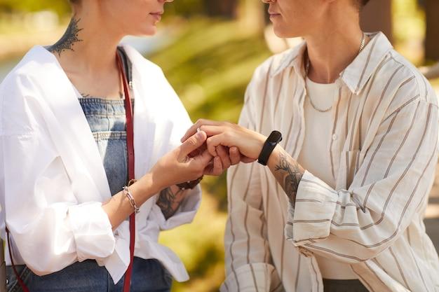 Duas jovens lésbicas estão noivas colocando anéis nos dedos uma da outra