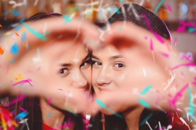 Duas jovens lésbicas fazem um coração com as mãos