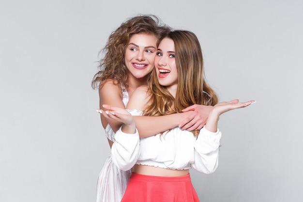 Duas jovens lindas loiras sorridentes abraçando em roupas da moda de verão. mulheres despreocupadas isoladas em fundo cinza.