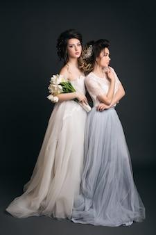 Duas jovens lindas mulheres elegantes em vestidos de noiva
