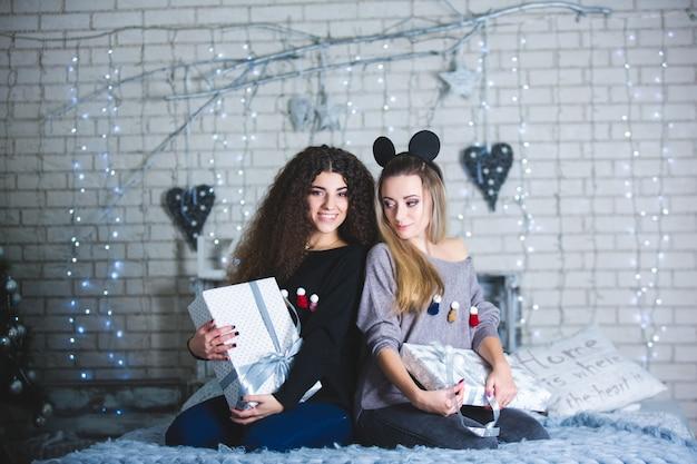 Duas jovens lindas mulheres sorridentes com presentes nas mãos.